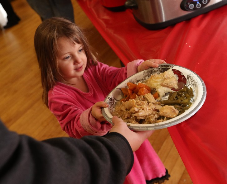There's anticipation in the eyes of Manon Ryder, 3, as she gets ready to enjoy a Christmas Eve dinner with her family at the Dom Polski Club in North Tonawanda. (Sharon Cantillon / Buffalo News)