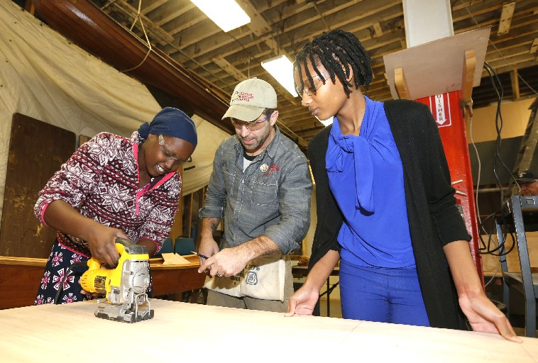 Buffalo Maritime Center Director Brian Trzeciak keeps an eye on Riverside Institute of Technology student Florence Uwumahoro, 15, left, as she cuts marine-grade plywood that will go into the hull of a canoe while fellow student Ester Tuyizere, 15, steadies the piece. The students are part of the school's new 'blue economy' program. (Robert Kirkham/Buffalo News)