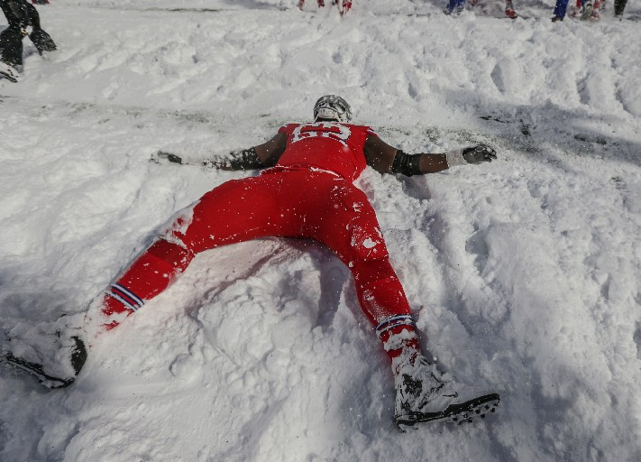 Vlad Ducasse makes a snow angel on the field after the Bills beat the Bolts in overtime. (James P. MCoy/Buffalo News)