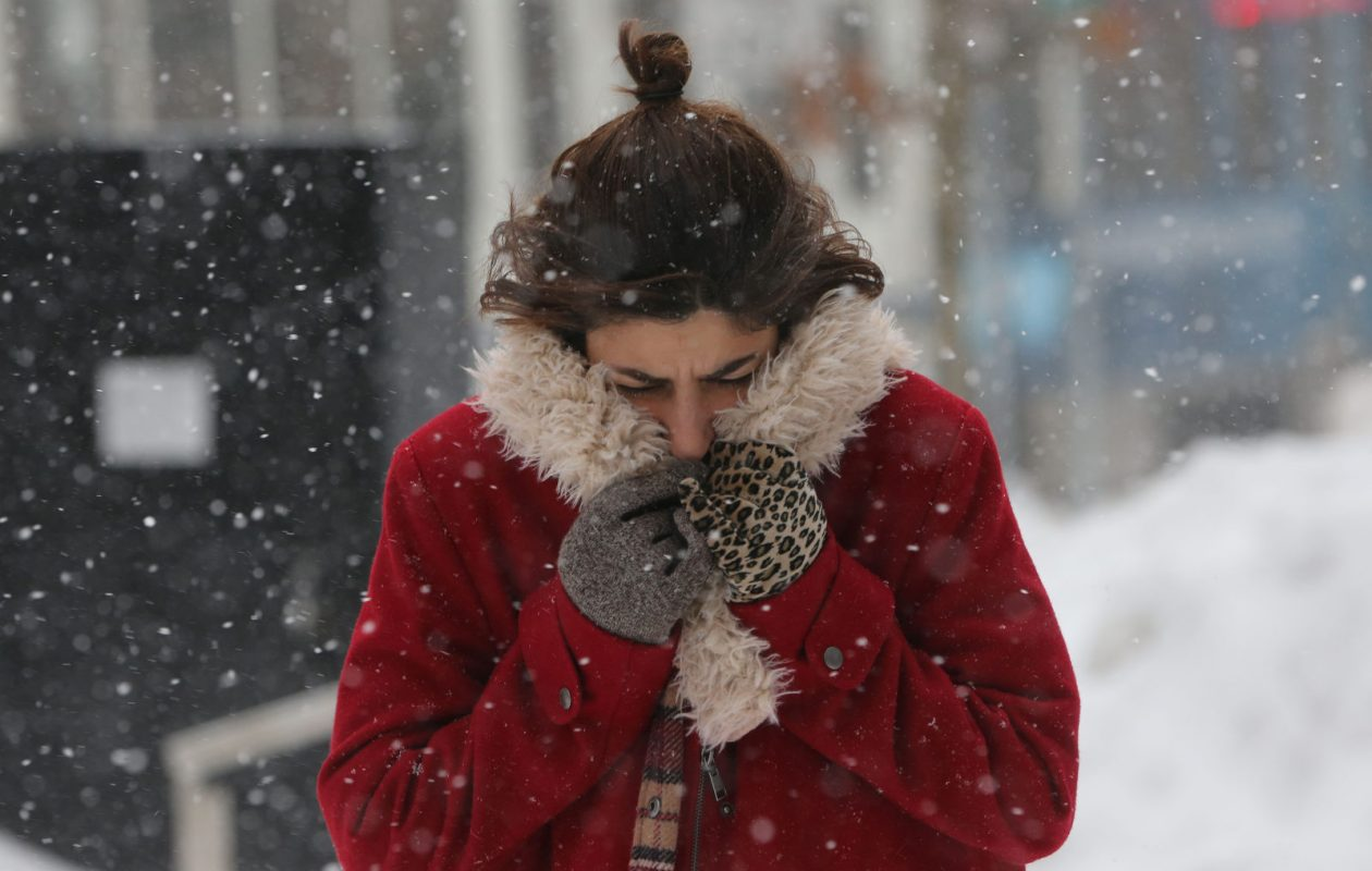 Rachel D'Alfonso braces herself against the cold as she walks down Main Street on her lunch break, Tuesday, Jan. 2, 2018. (Derek Gee/Buffalo News)