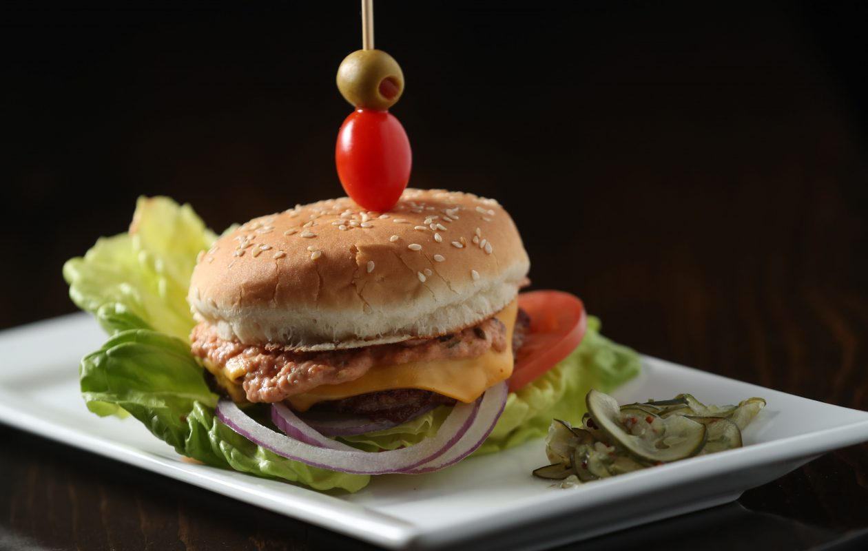 At $5, the Thrasher Burger is 'a bar snack star.' It's a 50/50 grind of top round and bacon, lettuce, tomato and onion and remoulade.  Cheese and extra patties may be added. (Sharon Cantillon/Buffalo News)