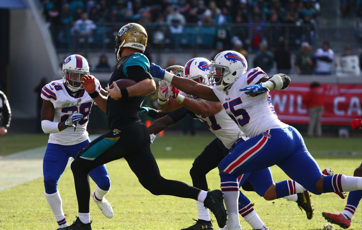 Jacksonville Jaguars quarterback Blake Bortles rushes for a first down past Buffalo Bills defensive end Jerry Hughes in the fourth quarter at EverBank Field in Jacksonville, Fla., on Sunday, Jan. 7, 2018. (James P. McCoy/News file photo)