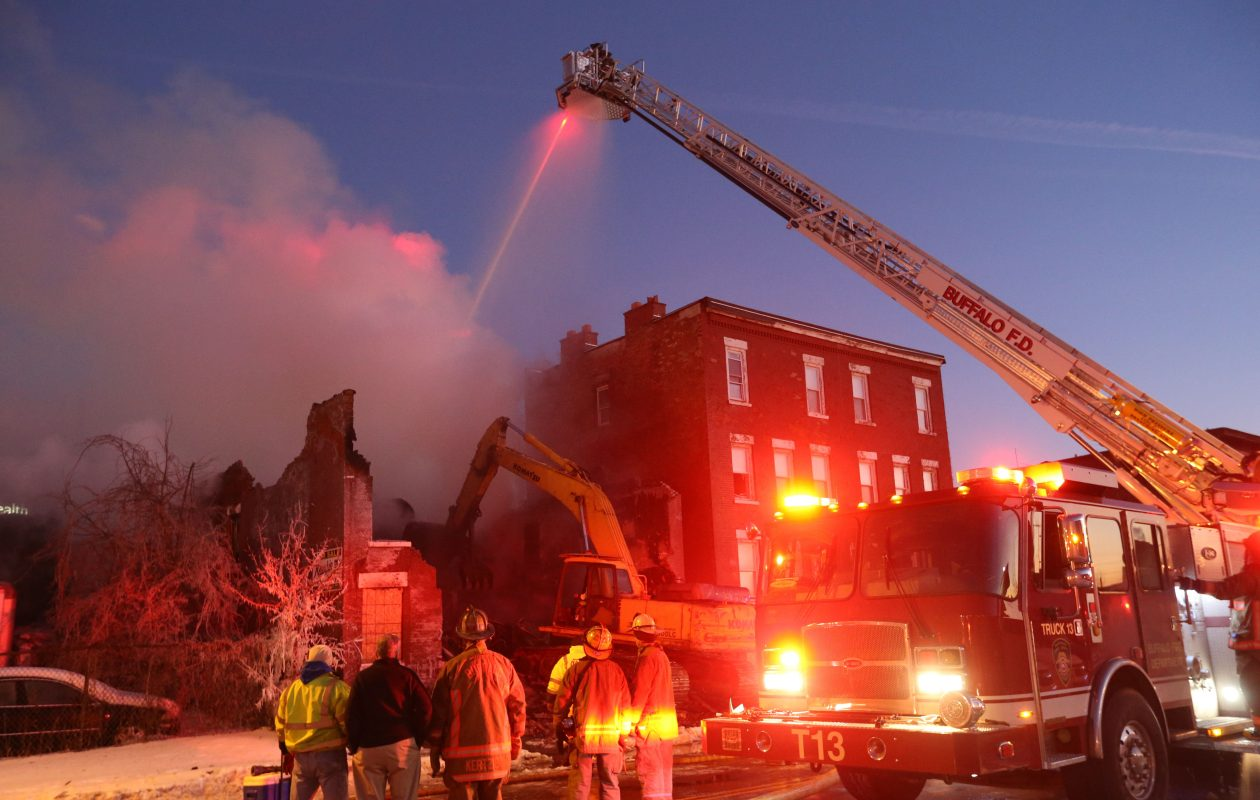 Buffalo Fire Department Ladder 13 sprays water on hot spots as an excavator knocks down the remnants of a brick building on Sycamore during an emergency demolition after an overnight fire destroyed the vacant building, Wednesday, Jan. 10, 2018.  (Derek Gee/Buffalo News)