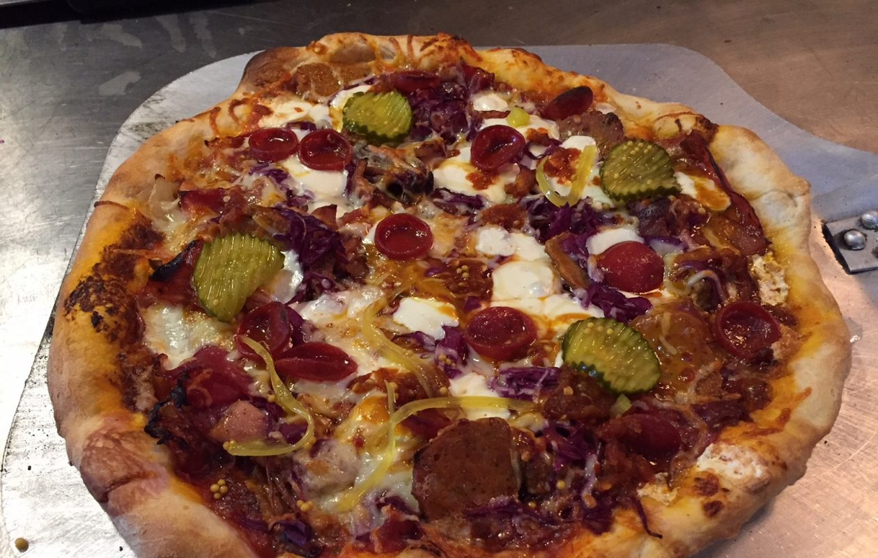 The pizza special Notorious P.I.G. features five meats and is topped with homemade pickles. (Elizabeth Carey/Special to The News.)