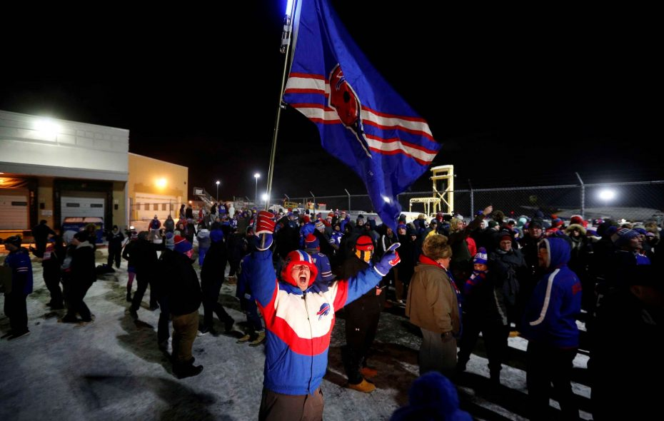 A Bills fan waves the team flag as hundreds welcomed the players home at the airport after their win in Miami, combined with Baltimore's loss, sent them into the playoffs — and began a week of local hysteria. (Derek Gee/Buffalo News)