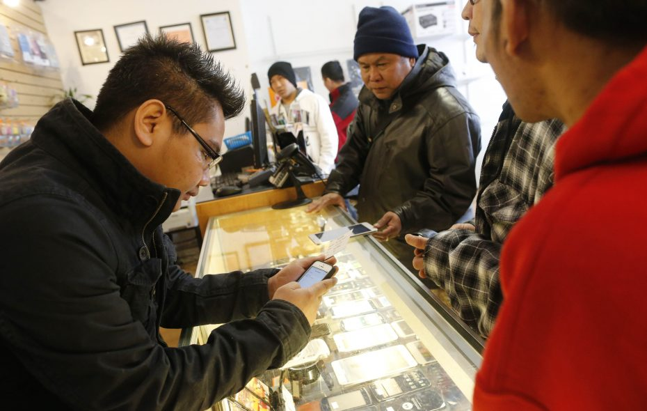Aung Kaung Myat, a refugee from Burma and owner of the iT Garden on Grant Street, helps Burmese customers interested in new cell phones. It is the type of business Buffalo may see fewer of now that Trump administration policies have reduced the number of refugees coming to the city. (Derek Gee/Buffalo News file photo)