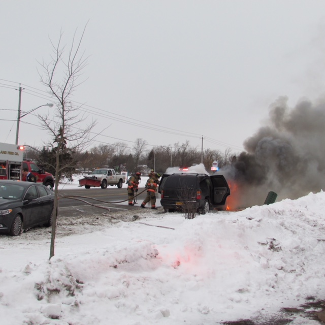 Firefighters try to extinguish a fire burning a minivan following a three-vehicle accident on Grand Island on Wednesday, Jan. 31, 2018.  (Provided by Grand Island Fire Department)