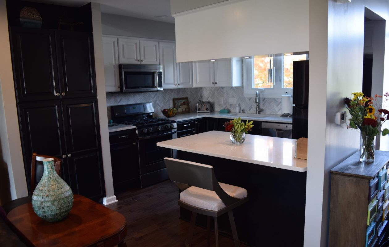 The kitchen cabinets were painted as part of an update. The top cabinets are white; the bottom ones are black. The appliances, quartz countertops and backsplash are new. The Downings have three grown children and five grandchildren.