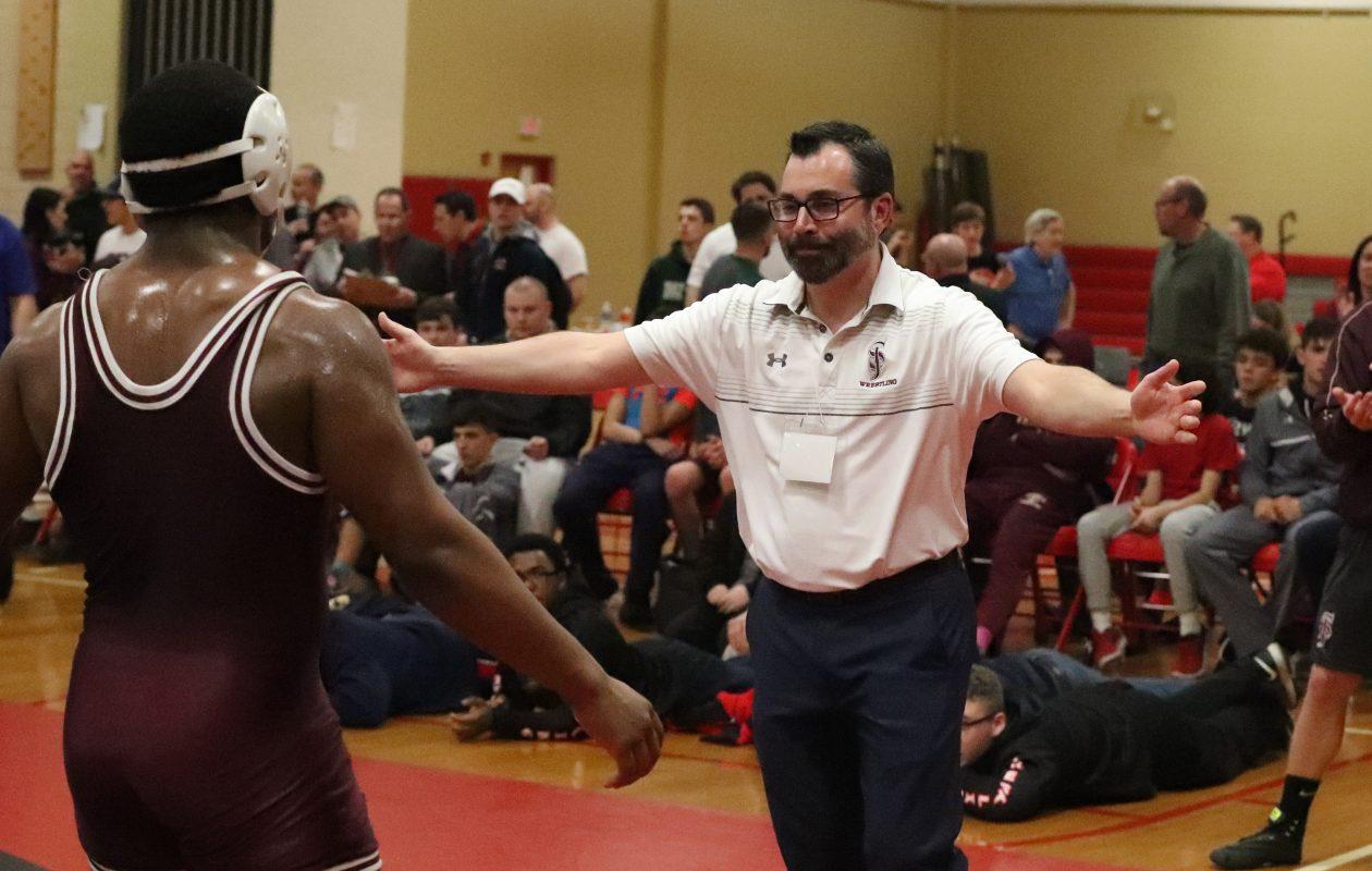 St. Joe's wrestling coach Pete Kennedy, pictured greeting Freddie Nixon after Nixon won a state Catholic title last year. (James P. McCoy/Buffalo News)