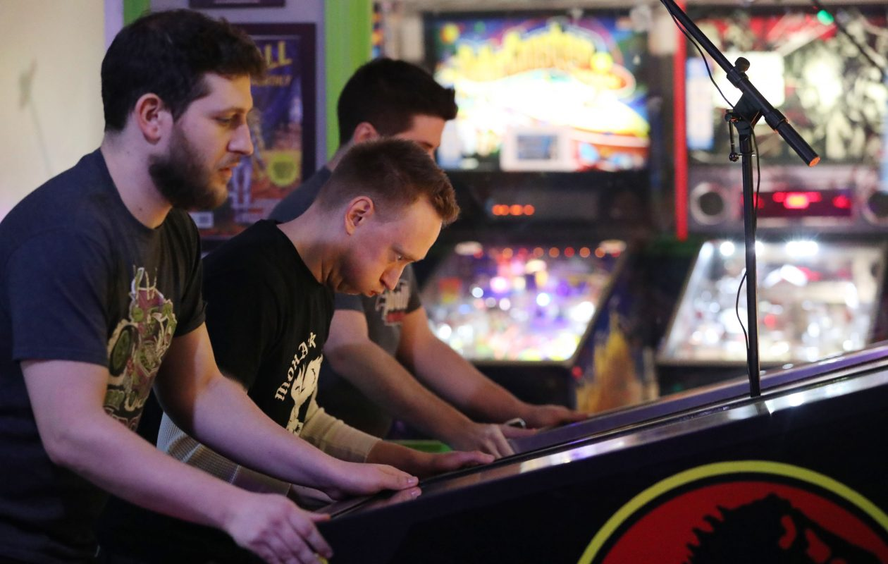 Nick Lane, center one of the two locals competing, is very expressive as he plays.  He's the President of Buffalo Pinball and is the tournament director.  On left is Nitzan Gabai of New York City. On right is Greg Poverelli, also of New York City.  (Sharon Cantillon/Buffalo News)