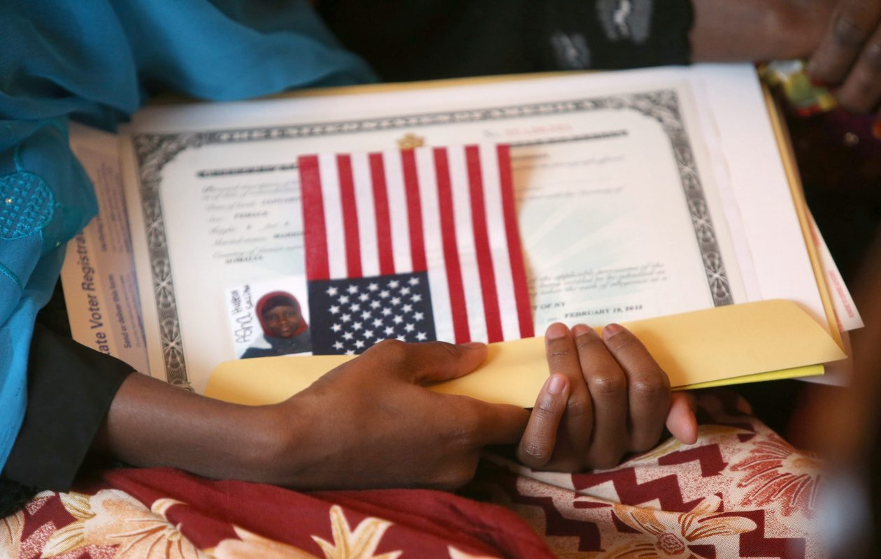 A new citizen from Somalia holds a U.S. flag and paperwork during a naturalization ceremony in a room at the Theodore Roosevelt Inaugural Site in Buffalo in 2013. (Robert Kirkham/Buffalo News file photo)