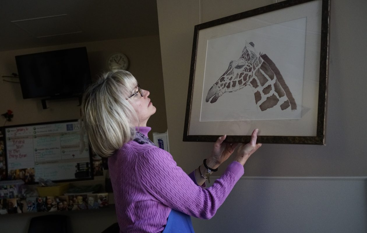 Roswell Park Comprehensive Cancer Center volunteer Julie Legters hangs a drawing in a patient's room on Tuesday, Jan. 16, 2018. (Derek Gee/Buffalo News)