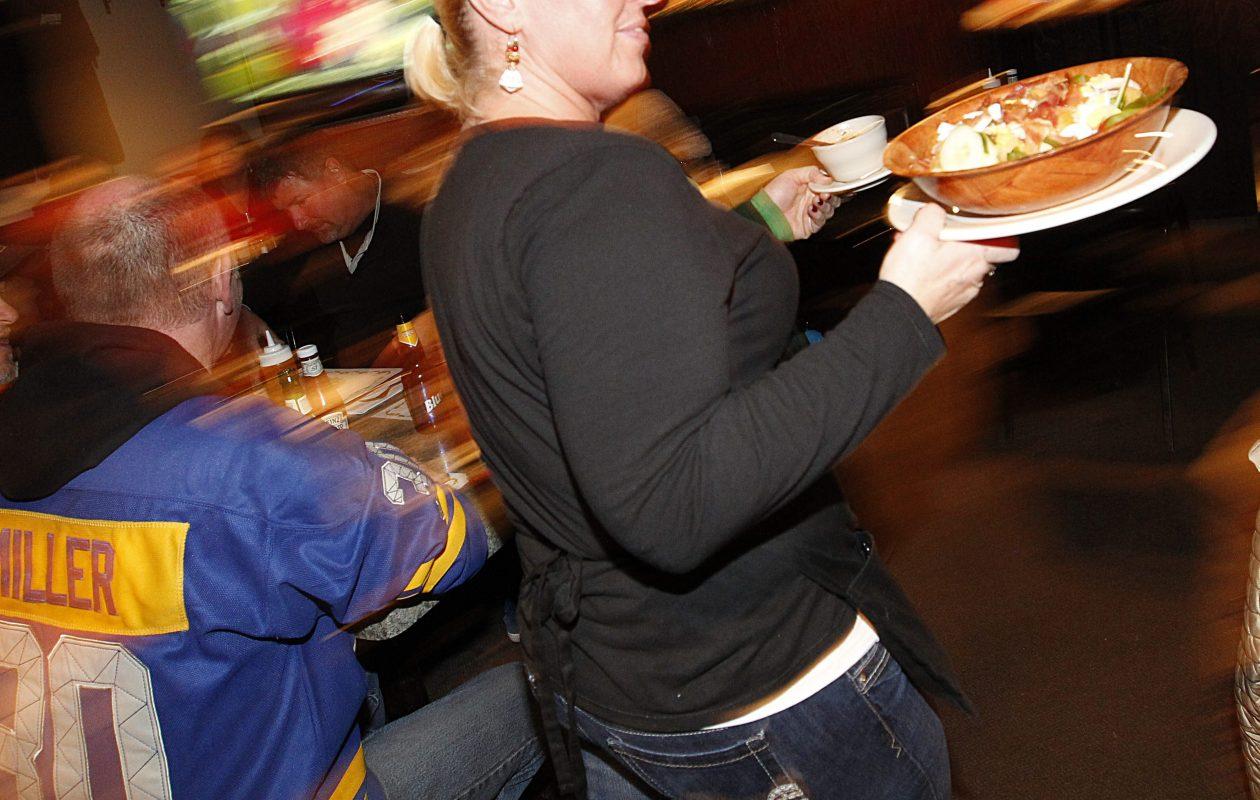 A waitress serves up a dinner at Washington Square Bar & Grill in Buffalo.  (Sharon Cantillon/Buffalo News file photo)