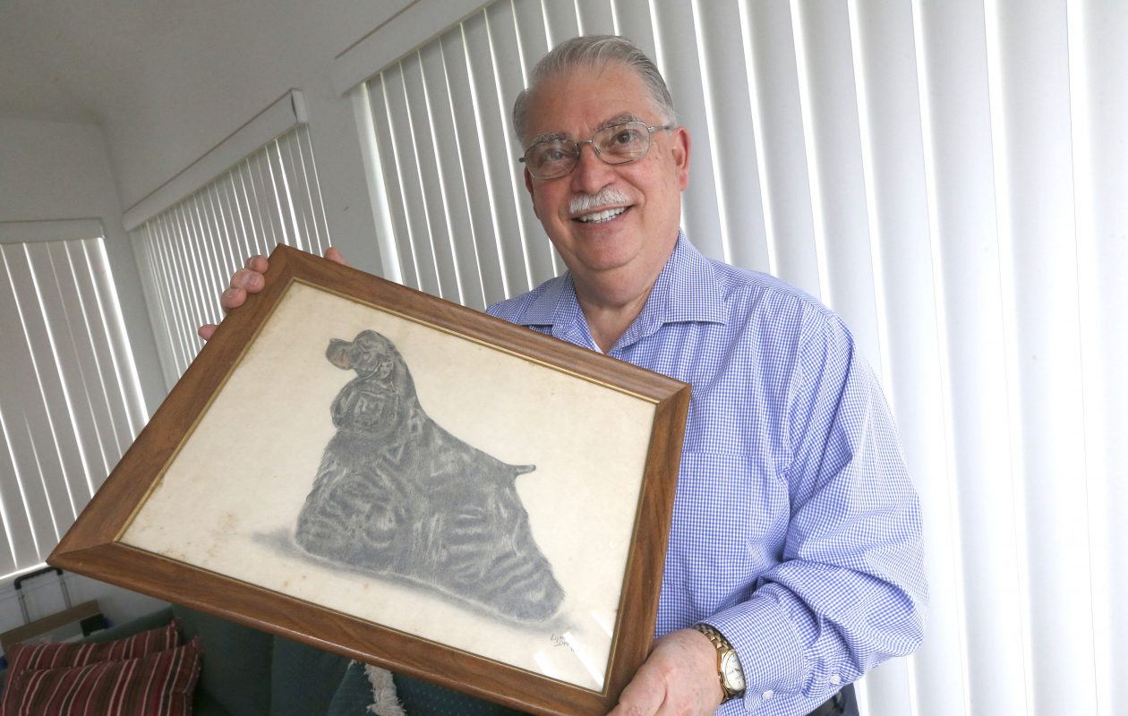 Westminster Dog Show judge Robert Ennis holding a charcoal drawing of one of his favorite dogs, a cocker spaniel, at his Blasdell home. (Robert Kirkham/Buffalo News)