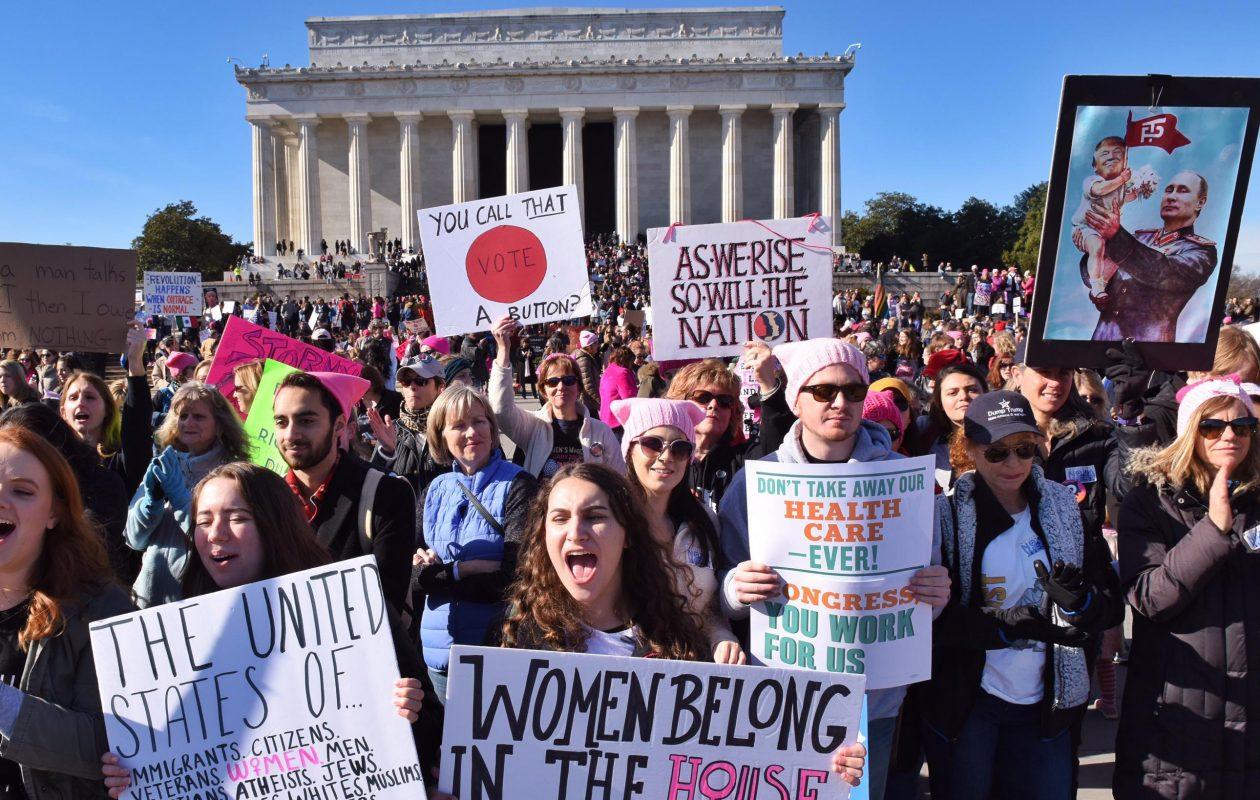 Demonstrators hold signs while cheering during the second Women's March on Washington at the Lincoln Memorial. (Washington Post)