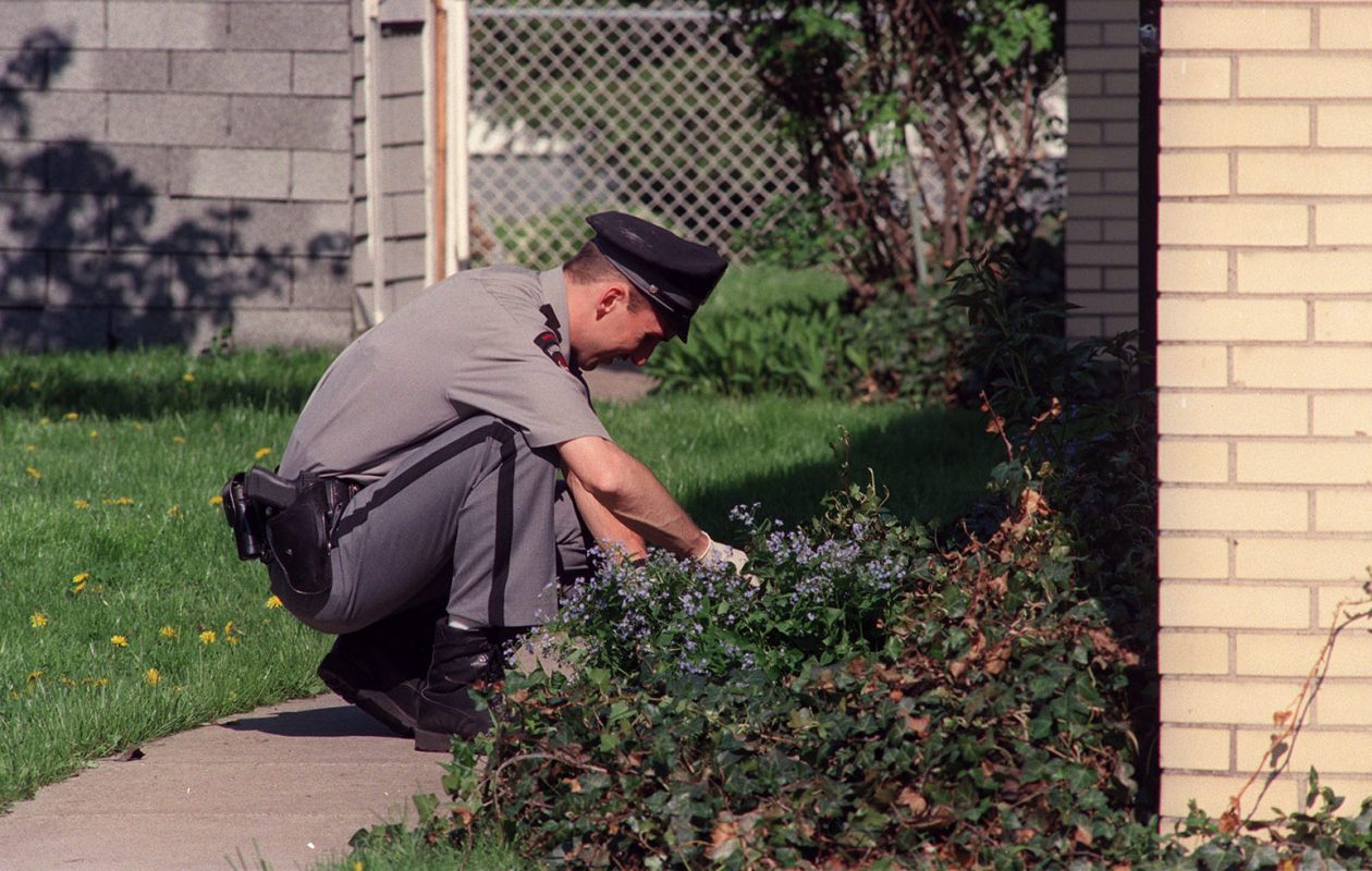 An Amherst police officer searches the back of the house at 90 Longmeadow on May 19, 1995. (News file photo)
