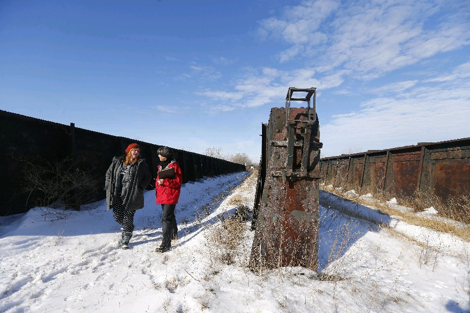 Sara Heidinger, left, a First Ward coffee shop owner and Nancy Smith, executive director of the Western New York Land Conservancy, explore an old rail bed hoping to be revived as an elevated trailway in Buffalo, a kind of 'High Line' near South Park  Avenue. (Mark Mulville/The Buffalo News file photo)