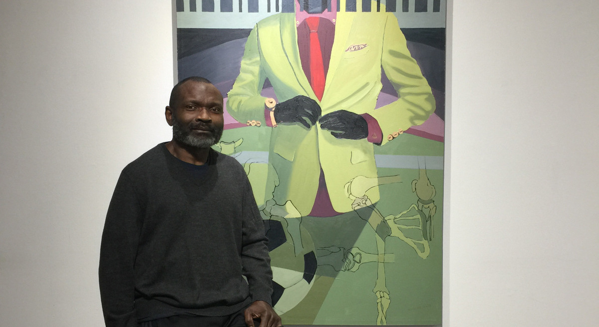 Buffalo painter George Afedzi Hughes sits with a recent painting on view in Buffalo Arts Studio as part of his solo exhibition.