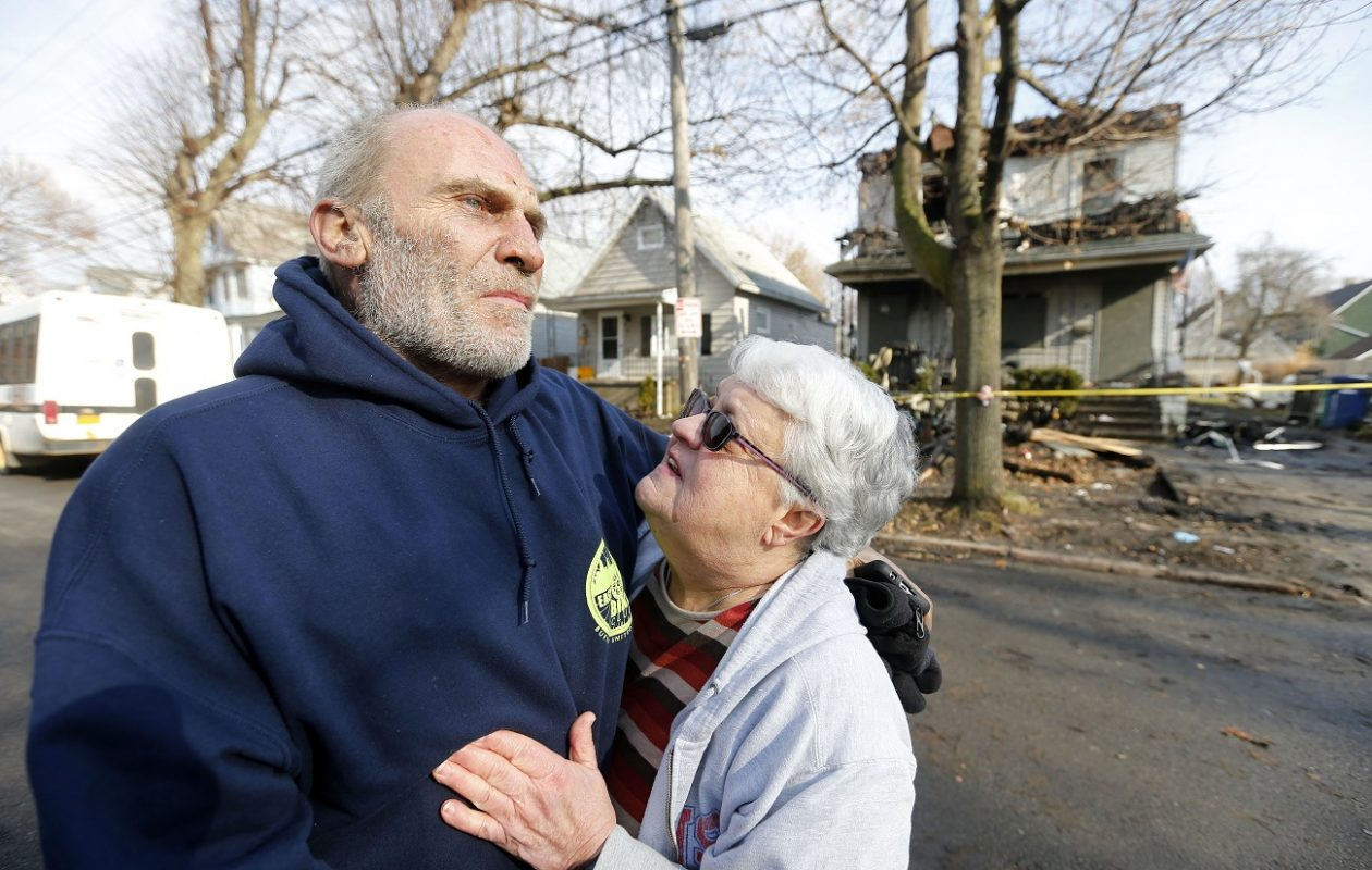 Joseph Conti is comforted by his neighbor Marilyn Ramsdell in front of his home on Benzinger Street in Buffalo's Lovejoy neighborhood on Monday, Jan. 29, 2018. The early morning fire took the life of Conti's 7-year-old son, Anthony. (Mark Mulville/Buffalo News)