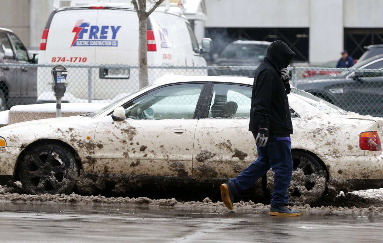 A person walks past a car that was spattered with slush on Court Street in Buffalo Thursday, Feb. 8, 2018.   (Mark Mulville/Buffalo News)