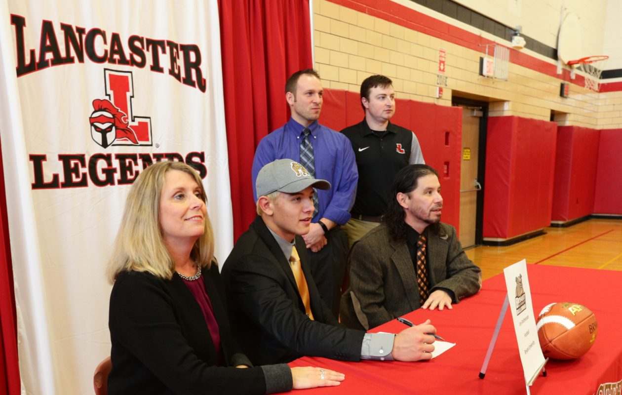 Lancaster's Joe Andreessen is surrounded by his mom, Jody, his dad, Paul, along with Legends head coach Eric Rupp and assistant Sean Bruso during Lancaster's National Signing Day ceremony Wednesday. (James P. McCoy/Buffalo News)