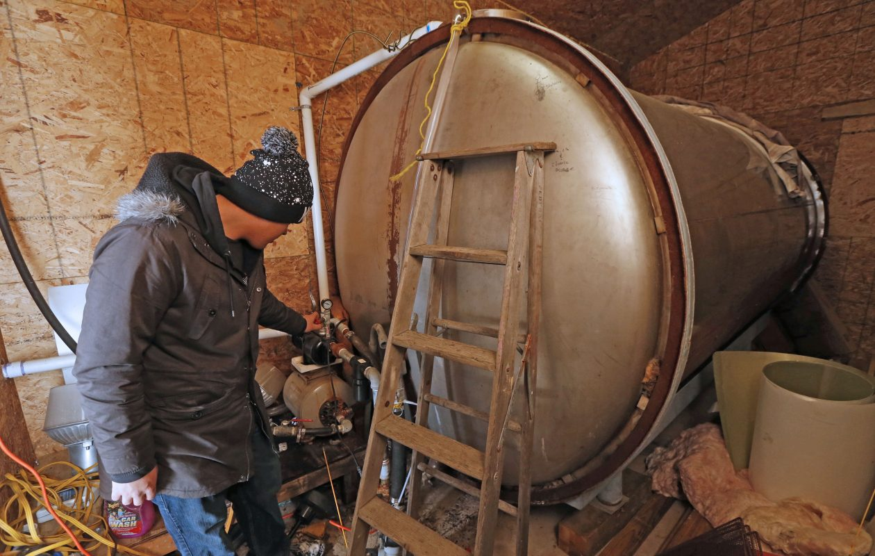 Ethan Rice, an employee at Patterson's Trading Post on Upper Mountain Road in Sanborn, checks the tank pressure on their 4,000-gallon stainless steel water tank that they periodically fill with trucked-in water to supply potable water to their store and two apartments.  (Robert Kirkham/Buffalo News)