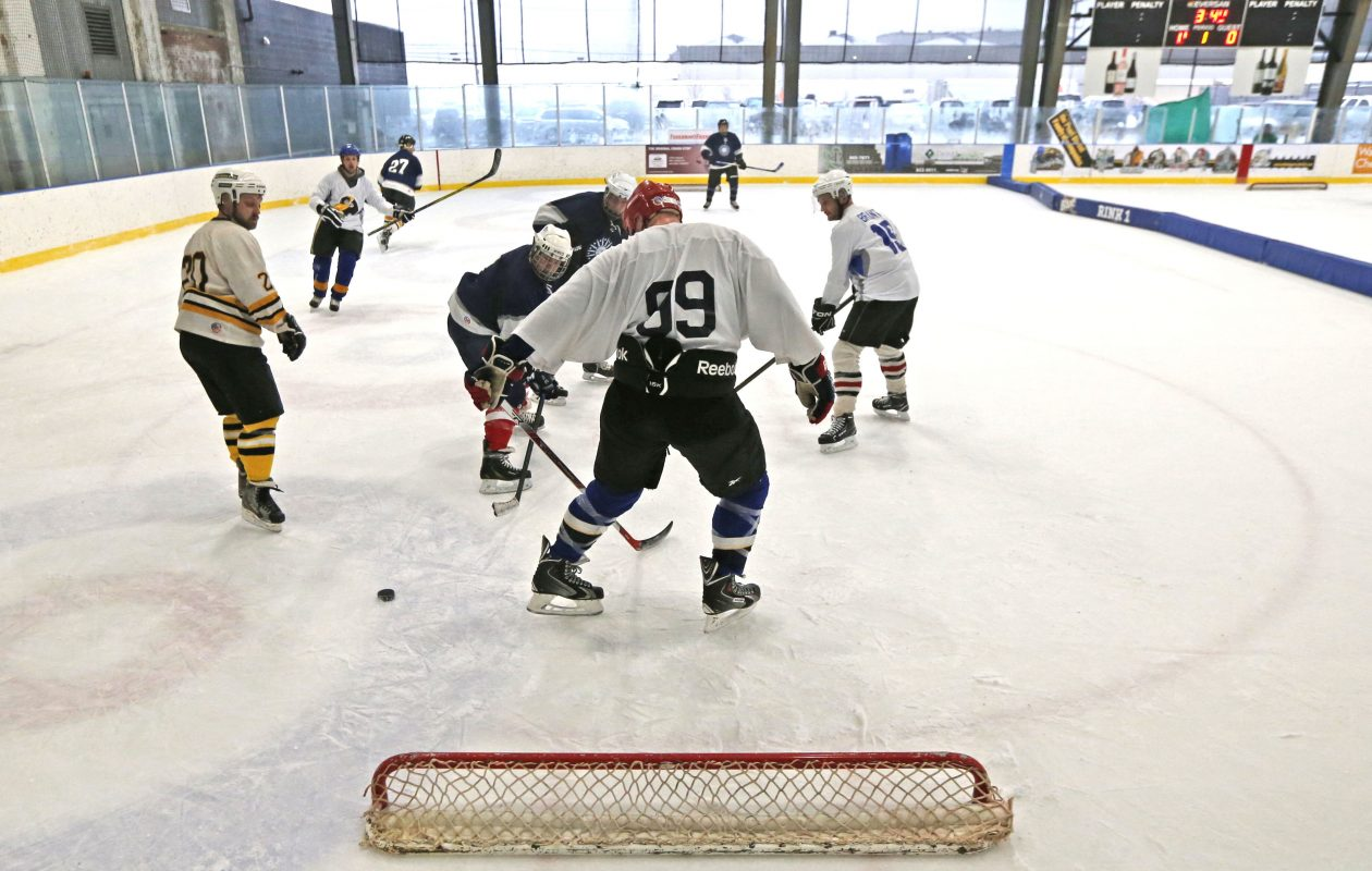 Members of the Buffalo DPW team, in dark blue, and The Ice Breakers tangle on the ice  during the pond hockey event at RiverWorks on Sunday, Feb. 11, 2018.  (Robert Kirkham/Buffalo News)