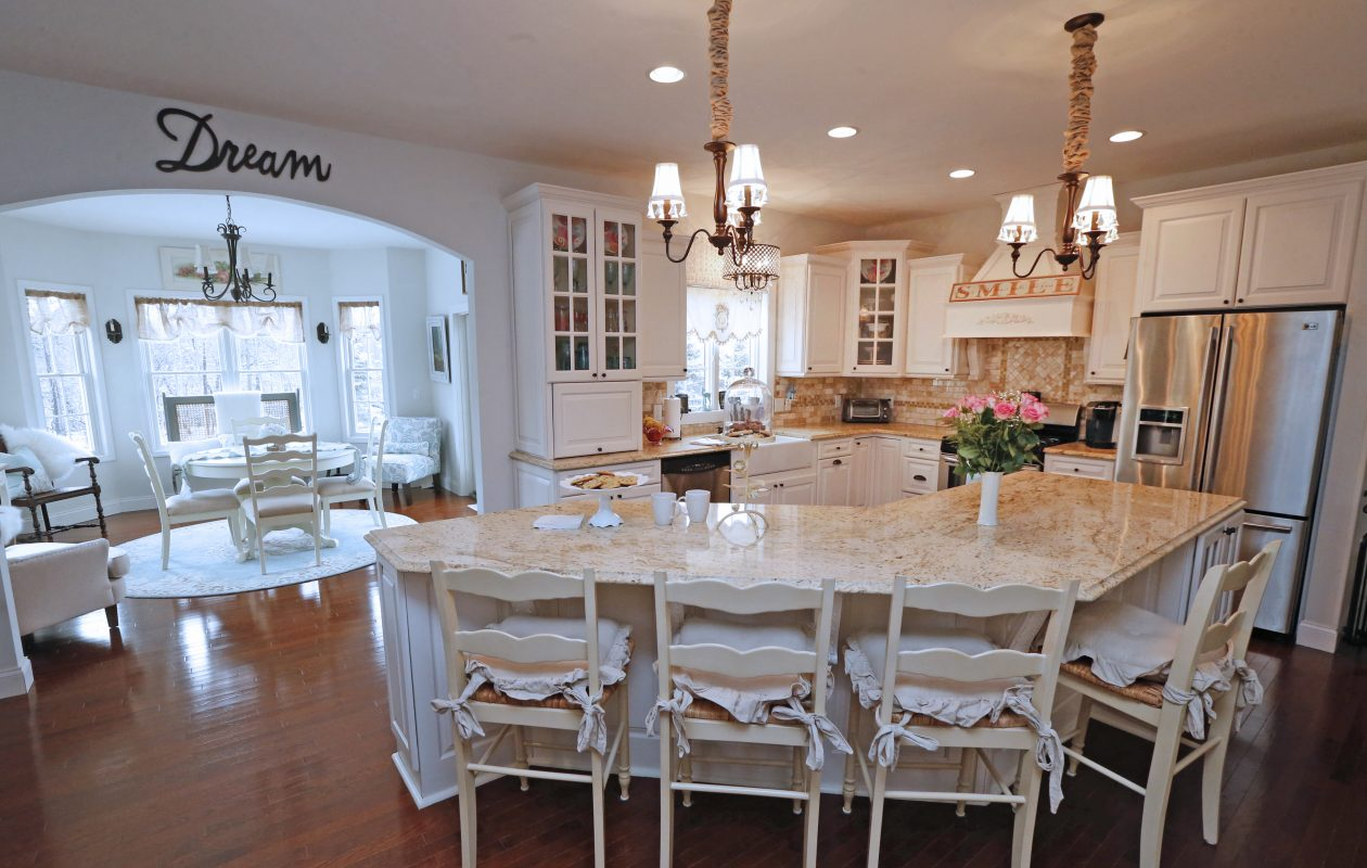 The King family's kitchen features an island, granite countertops and off-white cabinets. The kitchen opens to the 'morning room.' (Robert Kirkham/Buffalo News)