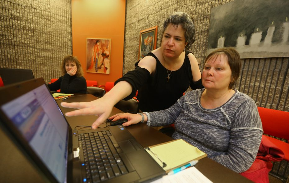 Sara Taylor, left, shows  Suzanne Muller of Niagara Falls how to get started in the Windows 10 program in a free class at the Niagara Falls Library.  Muller was one of five people who were confidently working through the program by the end of the class.  (John Hickey/Buffalo News)