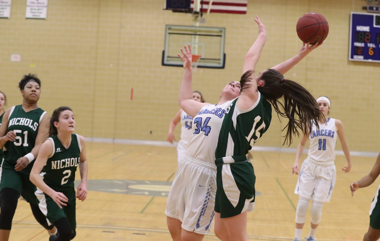 St. Mary's Caroline Zanghi rebounds the ball away from Nichols'  Jillian Niedzialowski in the first half of their game at Villa Maria Wednesday. (James P. McCoy/Buffalo News)