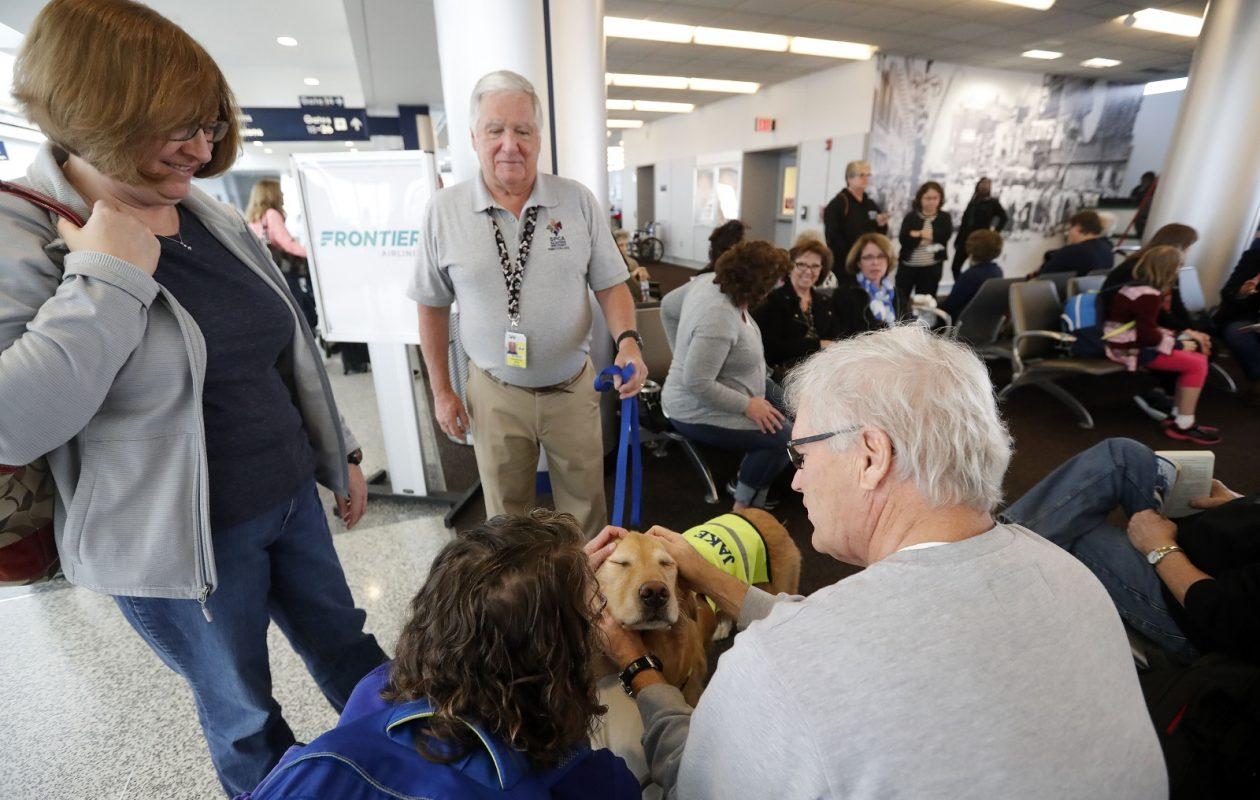 Al Monaco and his therapy dog Jake greet passengers at the Buffalo Niagara International Airport. (Mark Mulville/Buffalo News)