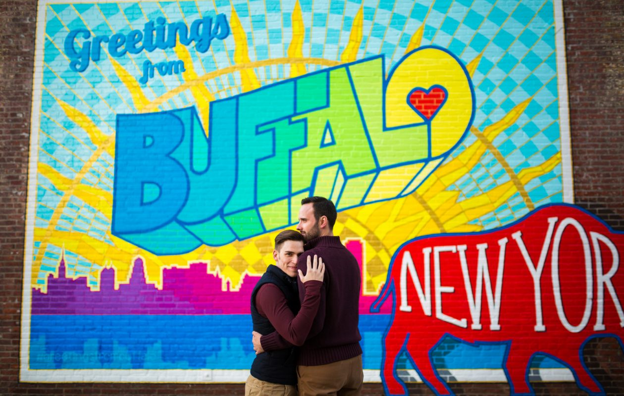Michael Deeb and Eric Weaver pose in front of the 'Greetings from Buffalo' mural  on Ellicott Street.(Photo courtesy of Erica Eichelkraut Zilbauer and City Lights Studio.)