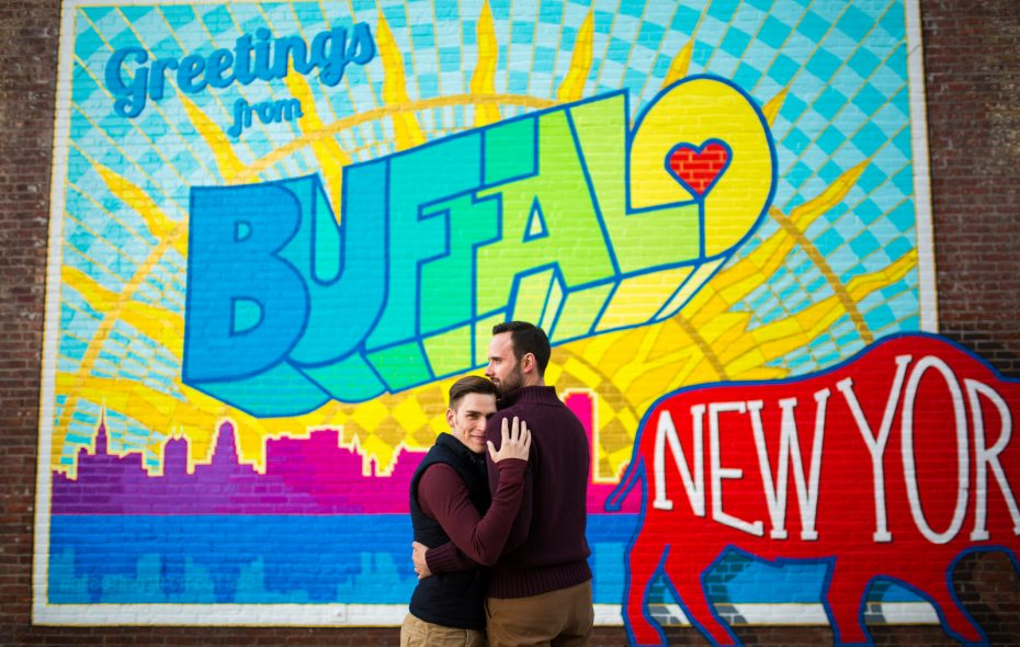 "Michael Deeb and Eric Weaver pose in front of the ""Greetings from Buffalo"" mural  on Ellicott Street.(Photo courtesy of Erica Eichelkraut Zilbauer and City Lights Studio.)"