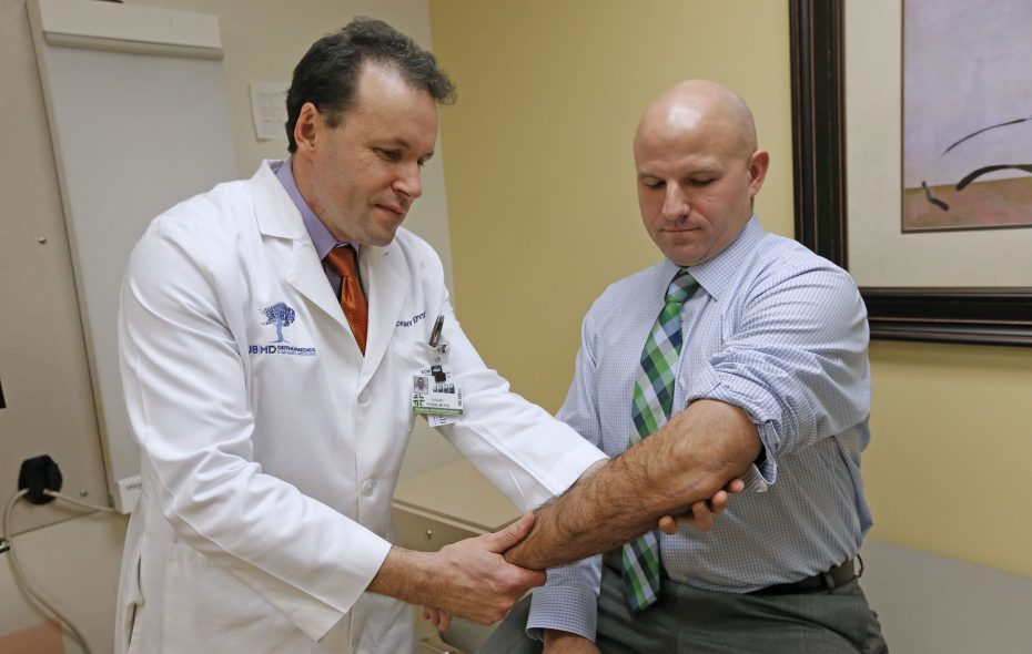 Christopher Rodler, right, credits Dr. Evgeny Dyskin, an orthopedic trauma specialist with UBMD Orthopaedics and Sports Medicine, left, with keeping him on the job and fully engaged with his family and athletic activities. (Robert Kirkham/Buffalo News)
