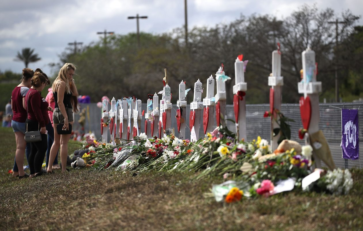 People visit a makeshift memorial setup in front of Marjory Stoneman Douglas High School on February 19, 2018 in Parkland, Florida. Police arrested and charged 19 year old former student Nikolas Cruz for the February 14 shooting that killed 17 people.  (Photo by Joe Raedle/Getty Images)