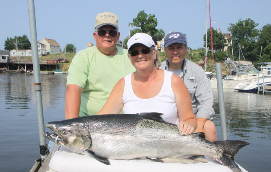 Sandy Brown of Clearfield, Pa., reeled in this 32-pound, 4-ounce salmon while fishing on the Niagara Bar to win the summer LOC Derby. Also pictured are her husband, Ed (left), and Joe Yaeger of Amherst.