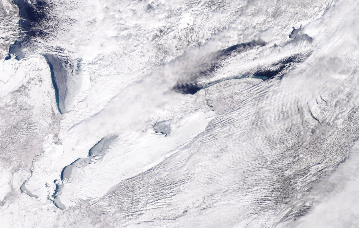 A satellite image from Tuesday shows that Lake Erie is encrusted in ice while Lake Ontario's open water remain a deep blue except for the long fetch of lake-effect snow over its west-to-east axis. (NASA/NOAA)