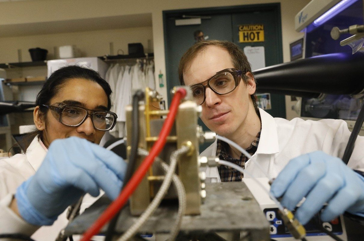 Timothy Cook, assistant professor of chemistry at the University at Buffalo and Ph.D. candidate Anjula Kosswattaarachchi work on a small redox flow battery they are testing in their lab. (Derek Gee/Buffalo News)