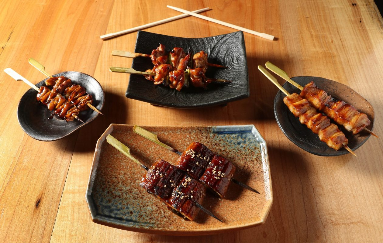 Among Sato Brewpub's selection of skewers,  clockwise from front, is unagi (eel), torikawa (crispy chicken skin),  negima (chicken thigh and scallion) and pork belly.  (Sharon Cantillon/Buffalo News)