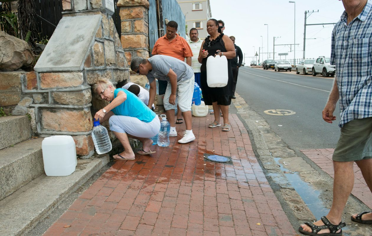 People collect drinking water from pipes fed by an underground spring in Cape Town. South Africa. (Getty Images)