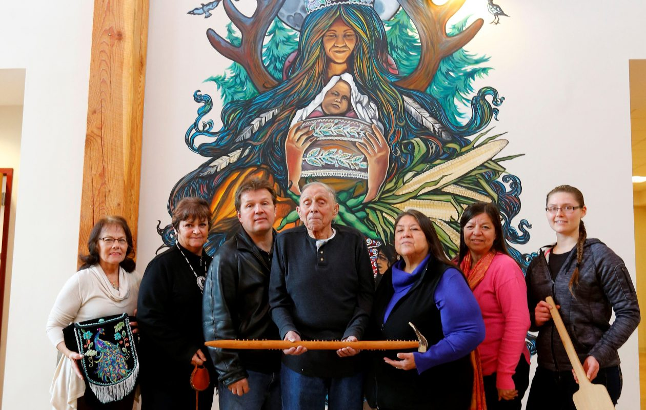Members of the History group of the Tuscarora Nation, are, from left, Judy Judware, Yehsenaruhcreh Wendy Bissell, Vince Schiffert, Chief Leo Henry, Gagehatdat Schandream, Angela Jonathan, and Taylor Hummel, stand in front a a mural at the Tuscarora Nation House. The group will host a 'Rez Life' event March 17. (Mark Mulville/Buffalo News)