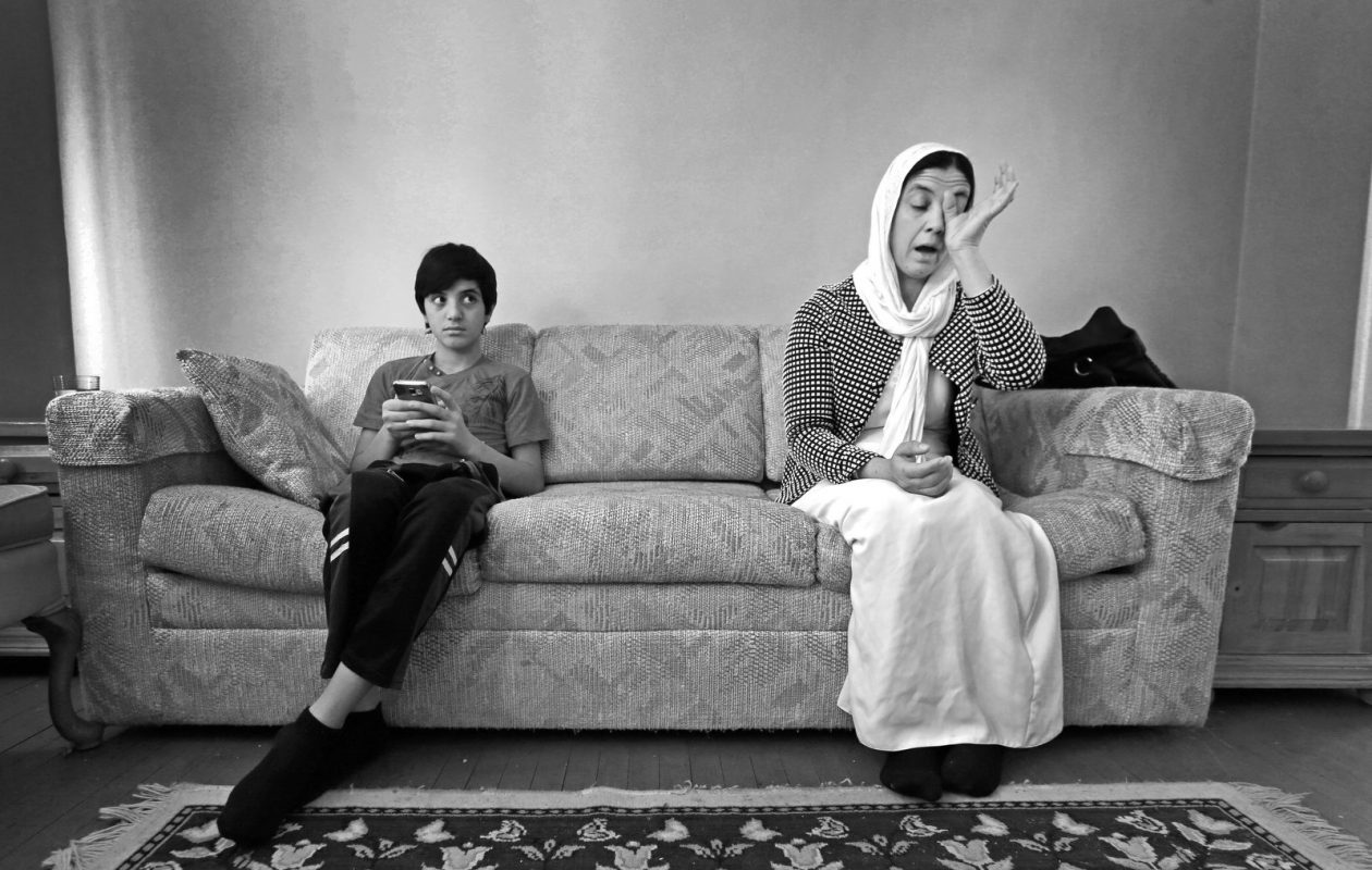 Yazidi refugee Mayha Alqasim, sitting with her son, 13-year-old Fadi Khaleel, wipes away tears  as she describes the family's ordeal. (Robert Kirkham/Buffalo News)