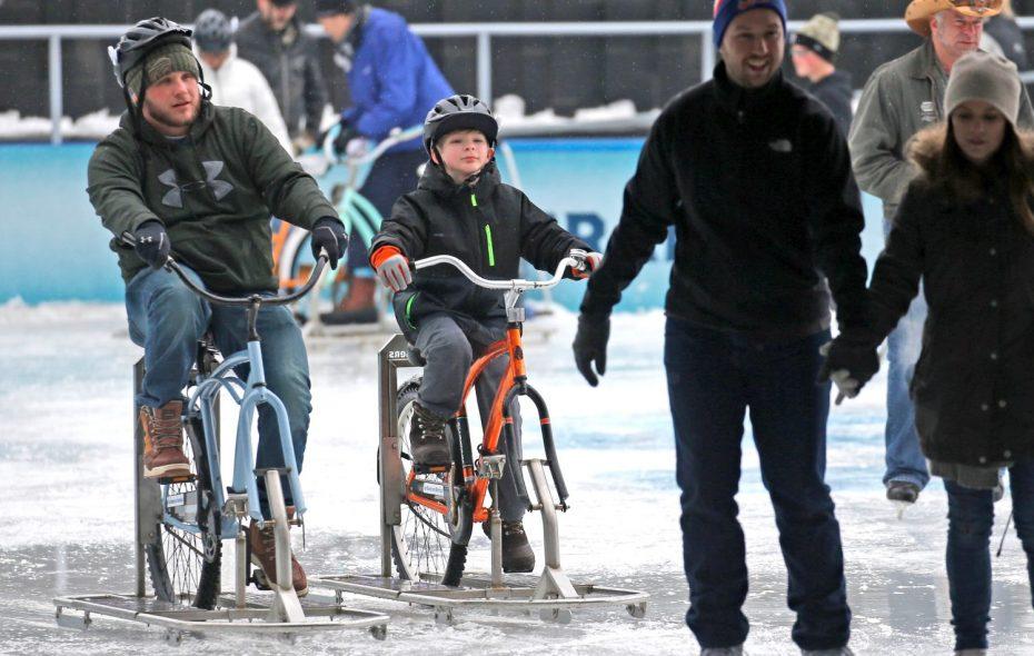 Scott Mackey and his son, Scott III, 10, check out the ice bikes. (Robert Kirkham/Buffalo News)