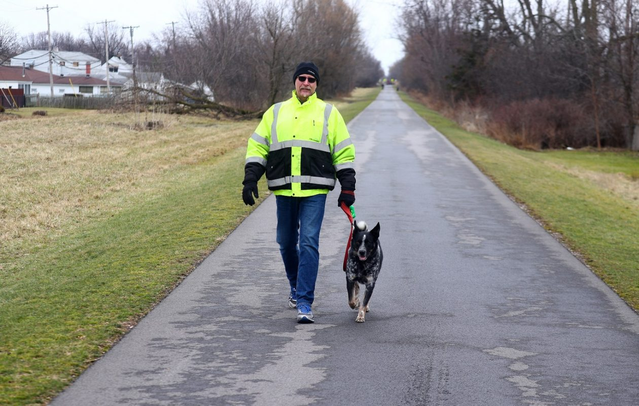 With sun and highs in the 50s, today's weather will be perfect for outdoor exercise. Here, Tim Kopasz, and his dog Buck walk on the Rails to Trails Bike Path in the Town of Tonawanda. (John Hickey/Buffalo News)