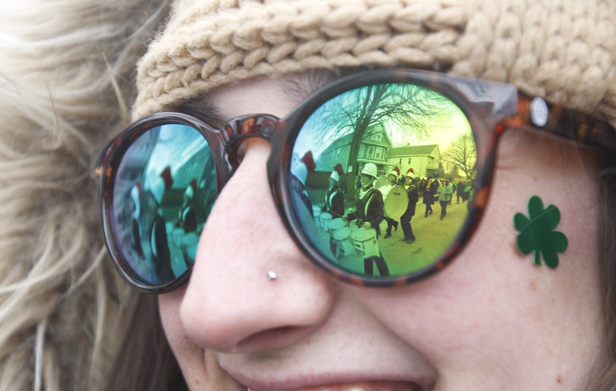 The Old First Ward parade is reflected in the sunglasses of Fallon Ormond, of South Buffalo, as she watches the parade progress last year. (Sharon Cantillon/Buffalo News file photo)