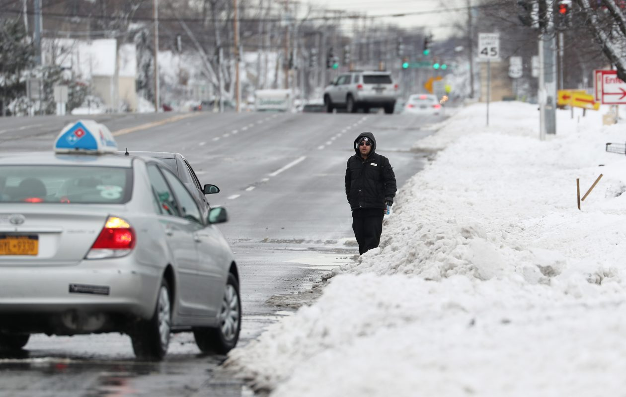 Hector Carillo walks on Maple Road, near where he works ,in a photo from early March. He had to step into the snow and wait for cars to go by at one point. (Sharon Cantillon/Buffalo News)