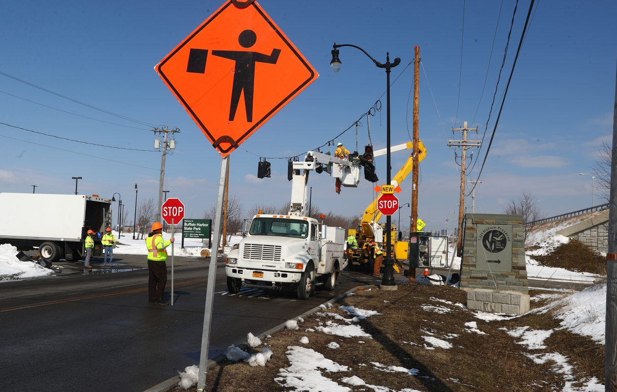 State Department of Transportation workers install temporary traffic signals on Fuhrmann Boulevard for the project on the Skyway.  (John Hickey/Buffalo News)