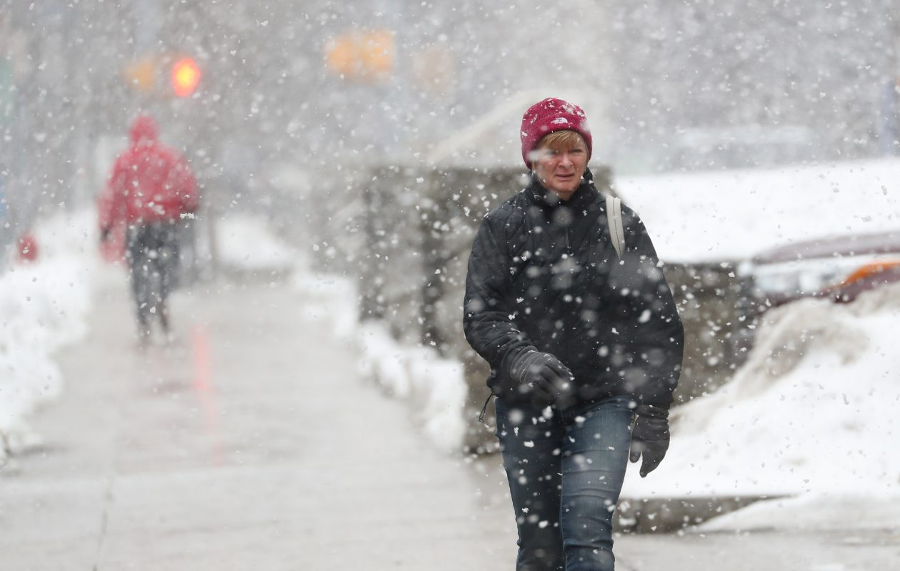 Theresa Baggott, walks along Eagle Street as large snowflakes fill the air in downtown Buffalo. The city's longtime snowfall record is under serious challenge from Erie, Pa.(Sharon Cantillon/Buffalo News)