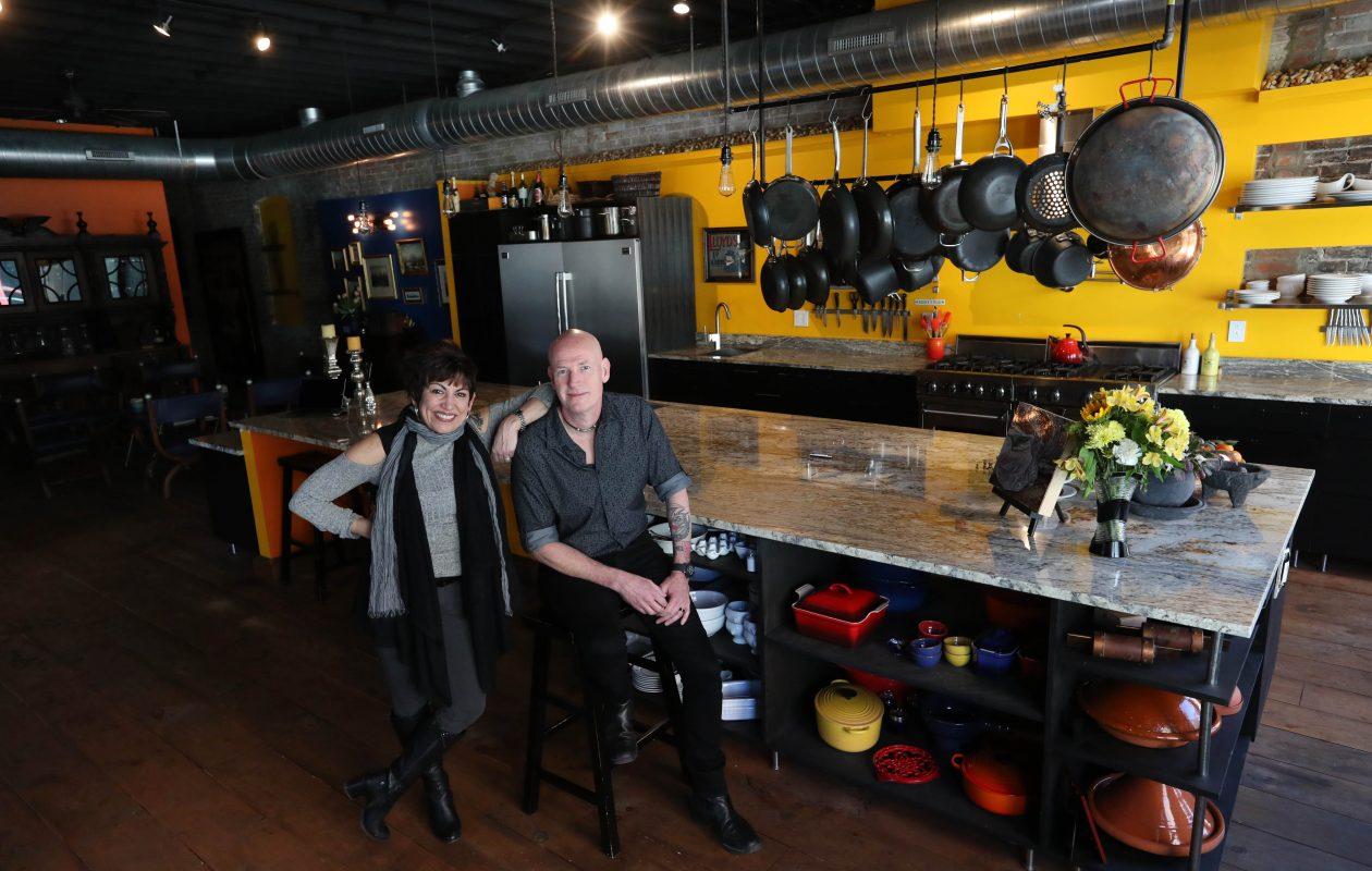 Sandra and Paul Wilkins   renovated the three-story building they bought in 2011 in downtown Buffalo.  They live on the two upper floors. Above, they are shown in the  large second-floor kitchen.  Their restaurant, Raclettes, is on the first floor. (Sharon Cantillon/Buffalo News)