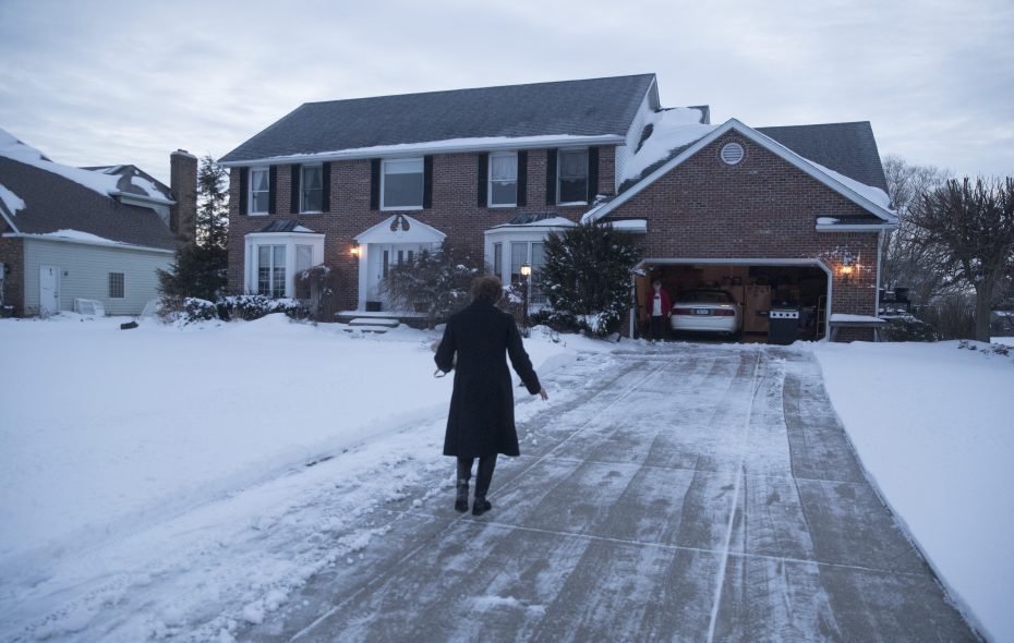 A woman delivers the morning newspaper to Gerri Mrugalski, waiting in the garage of her home in Clarence. (John Hickey/Buffalo News)